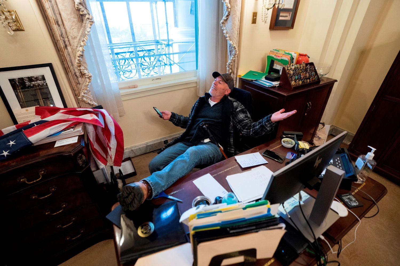 Un seguidor de Donald Trump, identificado como Richard Barnett, se sienta en el escritorio de la presidenta de la Cámara Baja, Nancy Pelosi, luego de irrumpir en el Capitolio.