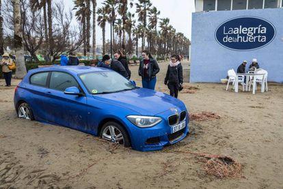 Un vehículo atrapado en la arena que invadió el paseo marítimo de Valencia,en la playa de la Malvarrosa, el pasado miércoles.