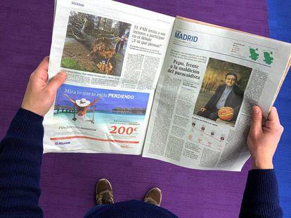 Un lector de El País con un ejemplar del periódico.