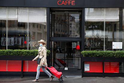 Una mujer camina delante de un restaurante cerrado en París, capital de Francia.