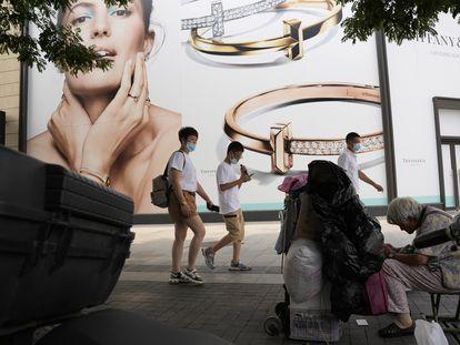 Un grupo de personas pasa junto a una mujer que recoge materiales reciclables en la calle comercial de Wanfujing en Pekín este miércoles