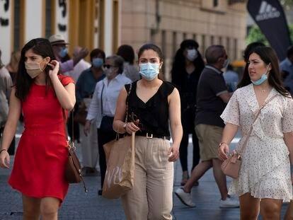 Tres jóvenes con mascarilla (una de ellas, en la barbilla), por una calle comercial de Sevilla, este miércoles.