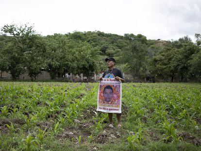 Clemente Rodríguez, padre de Christian, uno de los 43 normalistas, en su milpa con un cartel con la imagen de su hijo.