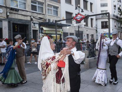 Baile de chulapos en la salida de la boca de metro de Lavapiés, durante las fiestas del barrio.