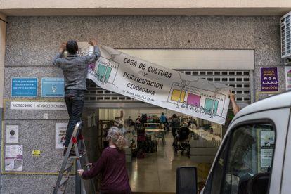 Tres activistas cuelgan el cartel de la Casa de la Cultura de Chamberí.