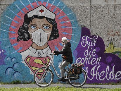 """Una mujer monta en bicicleta, en Hamm, al oeste de Alemania, junto a un mural de una enfermera en el que se lee: """"Para los verdaderos héroes""""."""