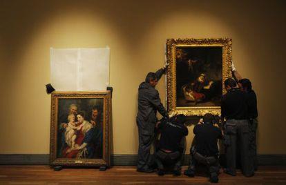 Un grupo de operarios en la exposición de El Prado 'Rembrandt, pintor de historias'.