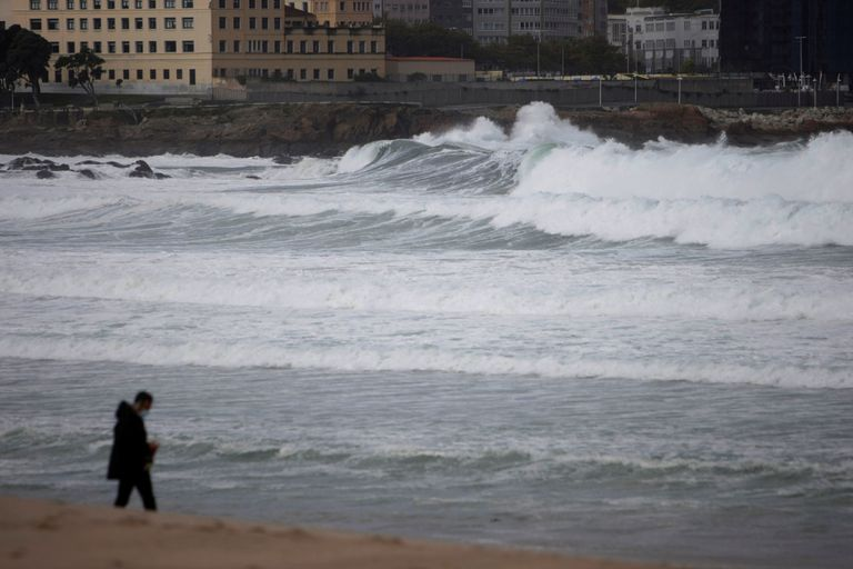 Un hombre pasea por la playa del Orzán en A Coruña, este viernes. Es una de las 29 provincias bajo aviso naranja.