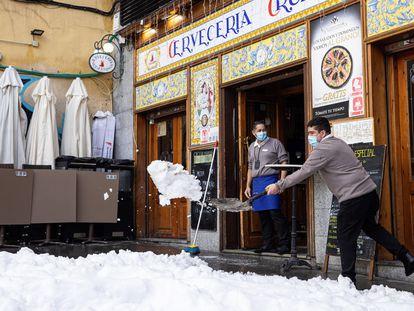 Trabajadores de un bar limpian de nieve la terraza de un local en Madrid, este domingo.