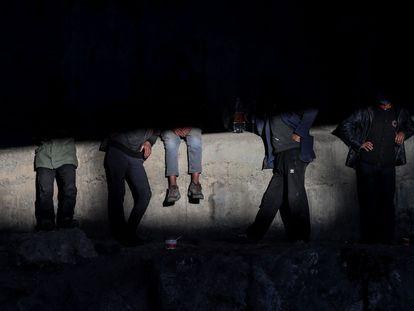Un grupo de inmigrantes sentados en un puente de la ciudad turca de Van, tras cruzar la frontera con Irán, este junio.