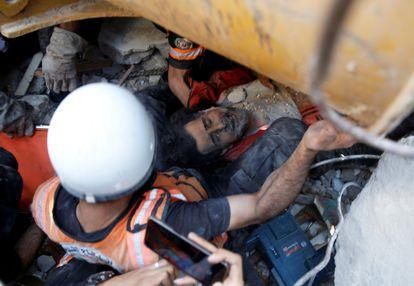 Un hombre es rescatado entre los escombros de un edificio en Gaza, este domingo.