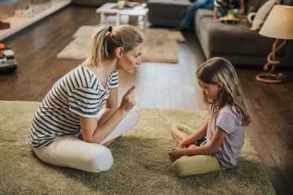 Una madre habla con su hija en el salón.