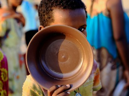 Un niño etíope, que ha huido de la guerra en la región de Tigray, lleva su plato mientras hace cola para obtener raciones de comida en el campamento de Um-Rakoba, en la frontera entre Sudán y Etiopía en el estado de Al-Qadarif, Sudán, el pasado 19 de noviembre de 2020.