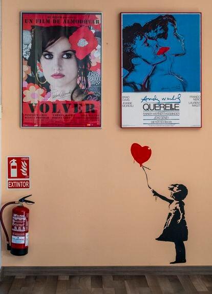 Una pared de la sede de Filmin con carteles de películas y el icónico dibujo de Banksy de la niña con el globo-corazón.