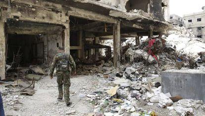 Un miliciano palestino camina entre los escombros del campo de refugiados de Al Yarmuk, en el sur de Damasco.