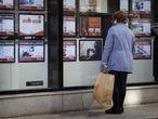 Una mujer mira el escaparate de una agencia inmobiliaria en Terrassa (Barcelona).
