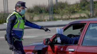 Un agente de la Policía Municipal de Madrid pide a un conductor el justificante que le permite moverse durante el confinamiento, el pasado abril.