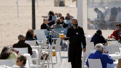 Un camarero atiende las mesas de una terraza de un bar en la playa de la Malvarrosa, en Valencia.