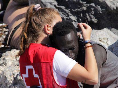 La trabajadora de Cruz Roja abraza al migrante que ha logrado cruzar uno de los espigones fronterizos de Ceuta este martes.