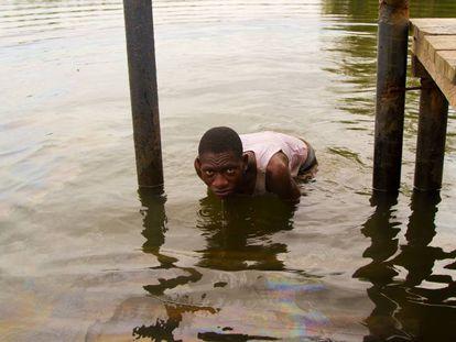 Un pescador del Delta del Níger, en Nigeria, sumergido en aguas contaminadas por vertidos de petróleo.