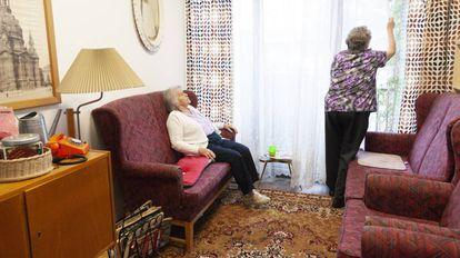 La señora Krumpelt (de oscuro) y la señora Bellmann (chaqueta blanca) en un saloncito todo decorado con objetos de la vida cotidiana de la antigua Alemania Oriental.