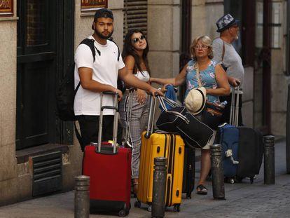 Varios turistas con maletas en el centro de Madrid.