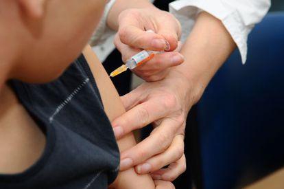 Un niño es vacunado en un hospital.