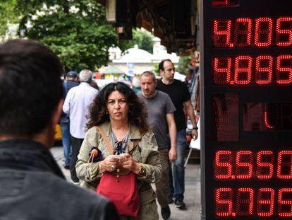Unos ciudadanos turcos pasan por delante de una pantalla que indica el cambio de dólares a liras, en Estambul.