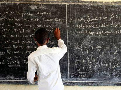 Un alumno escribe en la pizarra de su escuela en la región de Somaliland, en Somalia.