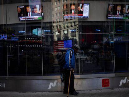 Un hombre pasa por delante de un escaparate con imágenes de un discurso del presidente de EEUU, Donald Trump, en Nueva York.