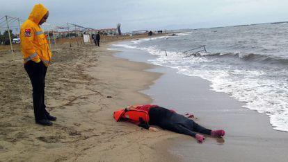 Un empleado del operativo de salvamento turco observa el cadáver de una mujer que llegó a la costa tras el naufragio de este martes en el Egeo.