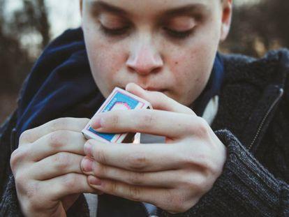 Un niño se enciende un cigarrillo.