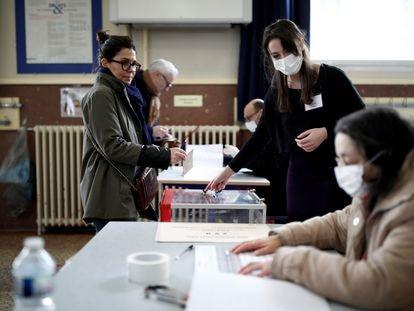 Varias personas con mascarillas, este domingo, en un colegio electoral de París.