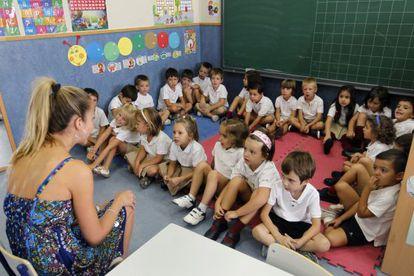 Un grupo de alumnos sigue las explicaciones de una profesora en un colegio en la comunidad de Madrid