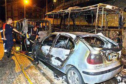 Los bomberos trabajan junto a uno de los vehículos incendiados el sábado en San Sebastián.