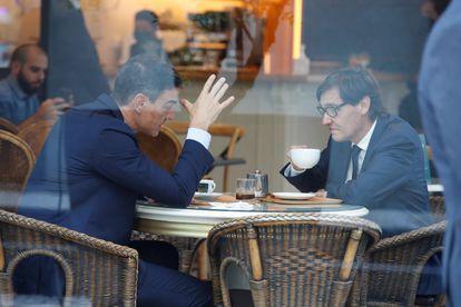 El presidente del Gobierno, Pedro Sánchez (izquierda), y el líder del PSC, Salvador Illa, charlan en una cafetería cercana a la sede de los socialistas catalanes en Barcelona.