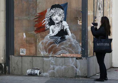 Una mujer observa el grafiti de Banksy que apareció en enero frente a la embajada francesa en Londres.