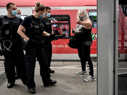 Policías en Colonia (Alemania) reprenden a una mujer por no llevar mascarilla en el transporte público.