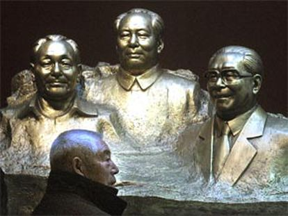 Un chino pasa junto a un grupo escultórico que representa a Deng Xiao Ping, Mao Zedong y Jian Zeming.
