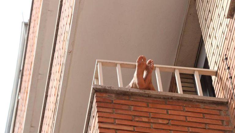 Una persona aprovecha para tomar el sol en su balcón, en Salamanca.