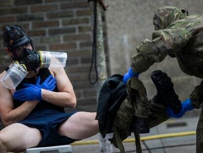 Dos militares proceden a descontaninarse tras desinfectar un centro de mayores de Vigo  (Pontevedra).