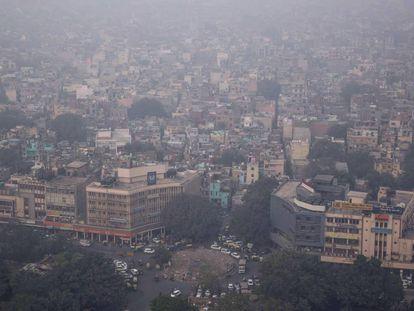 Nueva Delhi, cubierta de aire contaminado, durante el episodio de alerta del 1 de noviembre. A la izquierda, niños a la salida de un colegio de la capital, el pasado miércoles.