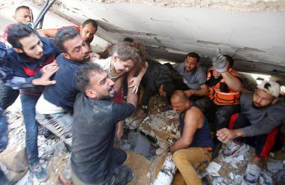 Palestinos rescatan a una niña entre los escombros de un edificio en Gaza, este domingo.