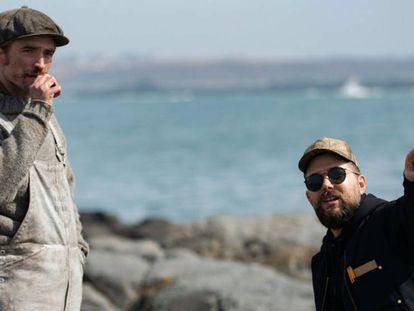 Robert Pattinson escucha las instrucciones de Robert Eggers (derecha), en el rodaje de 'El faro'. En vídeo, avance de la película.