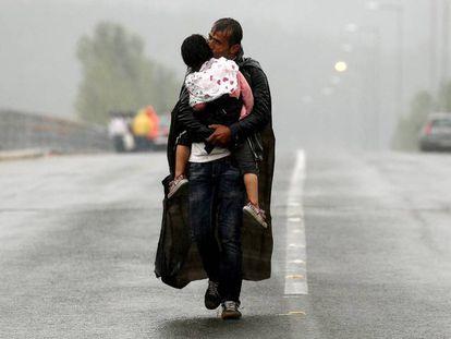 Un refugiado sirio besa a su hija mientras se acerca a la frontera entre Grecia y Macedonia en septiembre de 2015.