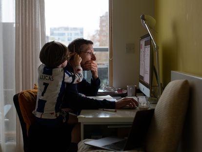 Un padre teletrabaja desde casa junto a su hijo, en Londres.