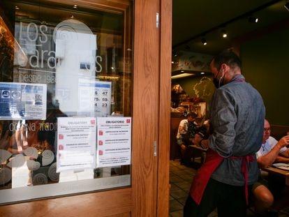 Carteles de indicaciones de obligatoriedad de presentar certificados antes de acceder al interior, en una marisquería de Santiago de Compostela