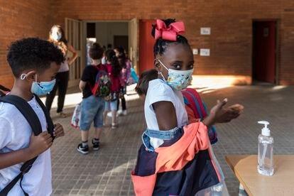 En la imagen, alumnas y alumnos de Primaria se aplican gel hidroalcohólico al entrar en la escuela.