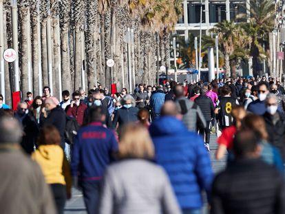 Traseuntes por el paseo marítimo de Barcelona, este sábado.