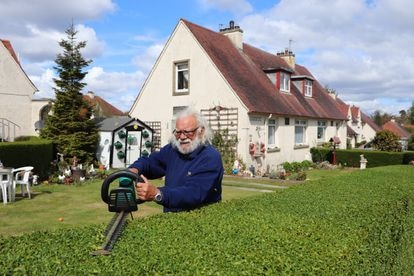 John Boath poda el seto de su jardín este miércoles en West Pilton, Edimburgo. / RAFA DE MIGUEL